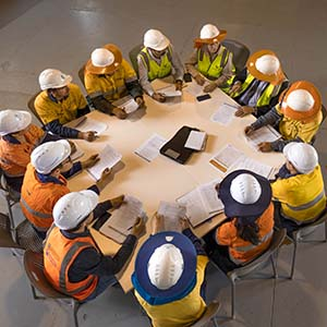 Team of people in hard hats sitting around table