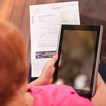 Person viewing bill holding a tablet device